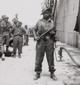 Sergeant Th. Nussy, leider van de baretten. Hij poseert in de haven naast de Kota Inten, Ambon, 14 mei 1950 (bron: MuMa)