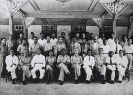 De Zuid-Molukken Raad (ZMR). Foto ter gelegenheid van het bezoek van NIT-minister Soumokil van Justitie (zittend 5e van links). Zittend v.l.n.r.: A. Bahasoan (administratief ambtenaar), D.J. Gaspersz (bestuursambtenaar), Pirsouw (bestuursambtenaar), mevr. C. Sahusilawane-Tomasoa, mr.dr. Chr.R.S. Soumokil, resident Vissers, D.P. Tahitoe (gouvernementsarts), Albert Wairisal, onbekend, P. Siregar. Tweede rij: 2e van rechts Tjokro (particulier onderwijzer Taman Siswa), 3e van rechts Alex Nanlohy, direct achter resident Vissers staat Huwae (voorzitter vereniging gepensioneerde militairen). Geheel achter onder het bord staat ir. J.A. Manusama. Rechts voor de paal S. Norimarna (administratief ambtenaar). De anderen zijn waarschijnlijk afgevaardigden van de zuidelijke eilanden. Ambon, 21/22 februari 1948 (bron: MuMa)