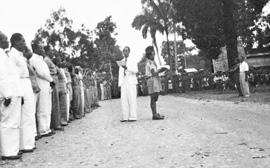 Het RMS-kabinet, aangetreden ter gelegenheid van de eerste vlaghijsing op de Esplanade. In het midden voor de rij ministers staat premier A. Wairisal die de proclamatietekst voorleest. Naast hem twee jongeren met de vlag. Ministers v.l.n.r.: eerste 3 mannen onbekend, vervolgens mr.dr. Chr.R.S. Soumokil (geheel wit), ir. J.A. Manusama, J. Manuhutu (in kaki pak), Alex Nanlohy (grijs met hoofddeksel). Ambon, 2 mei 1950 (bron: MuMa)
