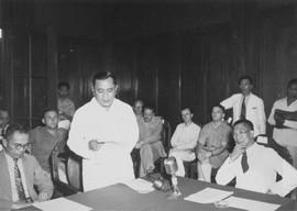 Nadjamoeddin Daeng Malawi tijdens zijn eerste rede als minister-president van de NIT. Rechts, zittend aan tafel: president Soekawati (bril, in het wit); links: minister E.D. Dengah (bril, in het grijs), Jakarta, 13 januari 1947 (bron: MuMa)