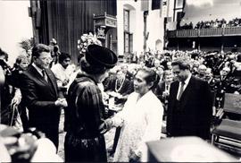 Koningin Beatrix reikt de herdenkingspenning (later: Rietkerkpenning) uit aan mevr. D.D. Behoekoe nam Radja-Muskita in de Eerste Kamer. Links minister drs. C.P. van Dijk, rechts ds. S. Metiarij. Den Haag, 1986 (bron: MuMa)