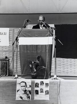 RMS-president in ballingschap ir. J.A. Manusama tijdens een RMS-herdenking in de Houtrusthallen, Den Haag, 1978. Op de voorgrond een portret van zijn voorganger Ch.R.S. Soumokil en foto's van de jongeren die omgekomen zijn bij de treinkaping bij De Punt (bron: MuMa)